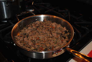 Once the entire meat mixture is browned, then you add the garlic, the seasoning, and the tomato paste